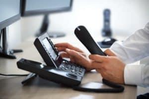 Telefon mit einer Männerhand, die gerade wählt